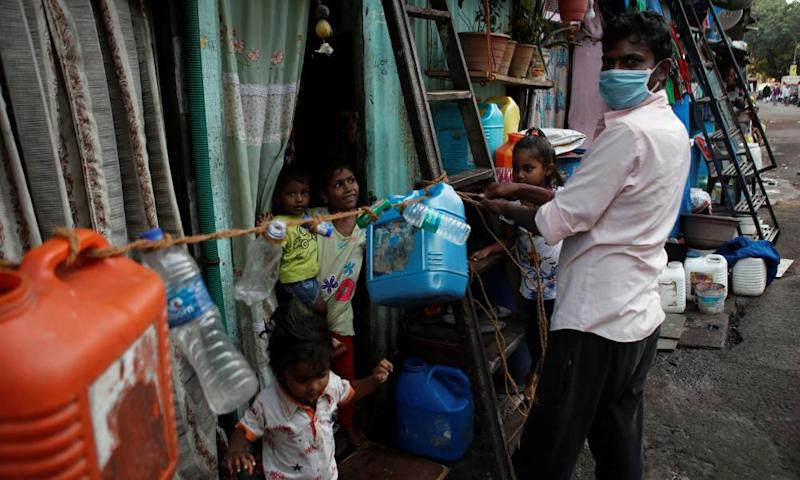 A man ties a rope outside his home in Dharavi to prevent his children from going outside, and other people from coming inside.