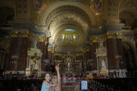 A woman holds a little girl inside the St. Stephen's Basilica in Budapest, Hungary, Friday, Sept. 10, 2021. Pope Francis is making his first foreign trip since undergoing intestinal surgery in July. His four-day visit to Hungary and Slovakia starting Sunday will not only test his health but also provide what may be one of the most awkward moments of his papacy — a meeting with Hungarian Prime Minister Viktor Orban, the sort of populist, right-wing leader Francis scorns. (AP Photo/Vadim Ghirda)