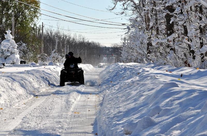A four wheeler drives down a street in the Lakeview neighborhood of Buffalo, New York on November 19, 2014 after a storm dropped nearly five feet of snow (AFP Photo/John Normile)
