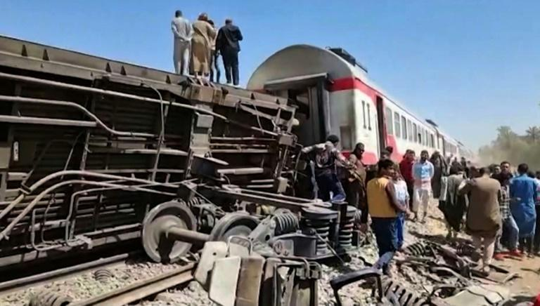 Axles, springs and twisted metal protrude from one of the railway carriages overturned in the collision in southern Egypt