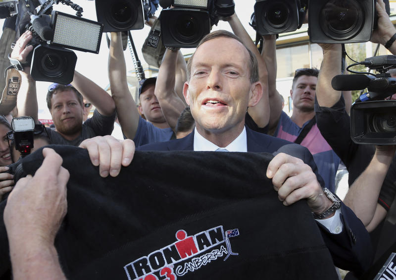 Australia's opposition leader Tony Abbott holds up an ironman towel at a polling station before he casts his vote at Freshwater Surf Life Saving Club in Sydney, Australia, Saturday, Sept. 7, 2013. Australians headed to the polls on Saturday in an election that pits a ruling party marred by infighting and a much-maligned carbon tax against a conservative opposition led by a man who has never been particularly popular and has long been polarizing.(AP Photo/Rob Griffith)