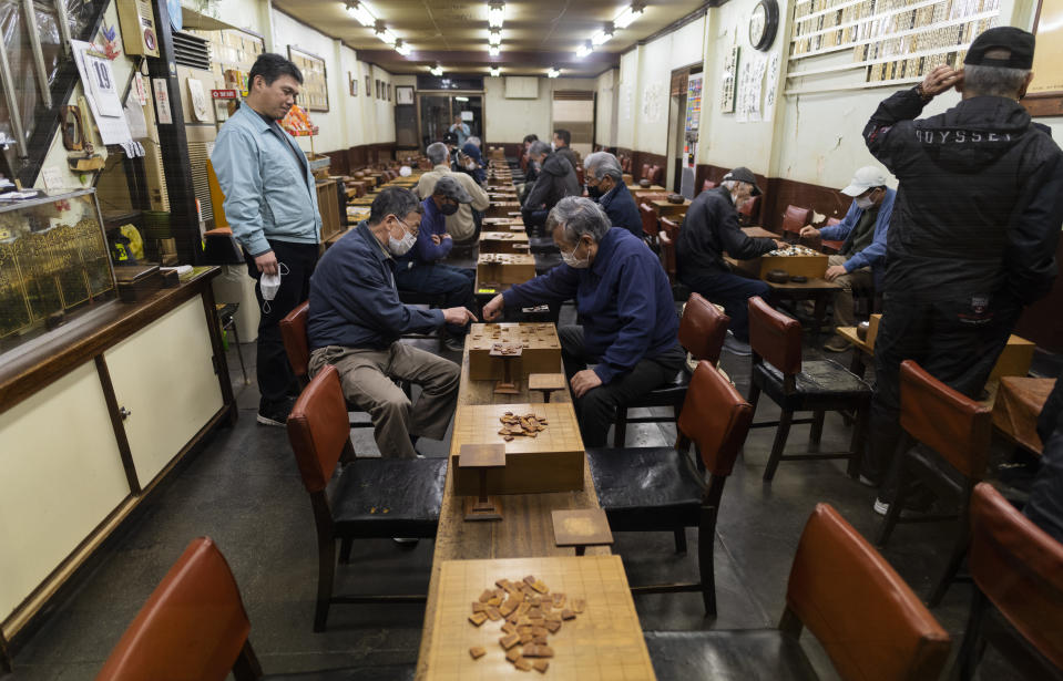 "People play ""shogi,"" a game similar to chess, before the parlor closes to follow the government measures against the coronavirus in Osaka, western Japan, Monday, April 19, 2021. (AP Photo/Hiro Komae)"