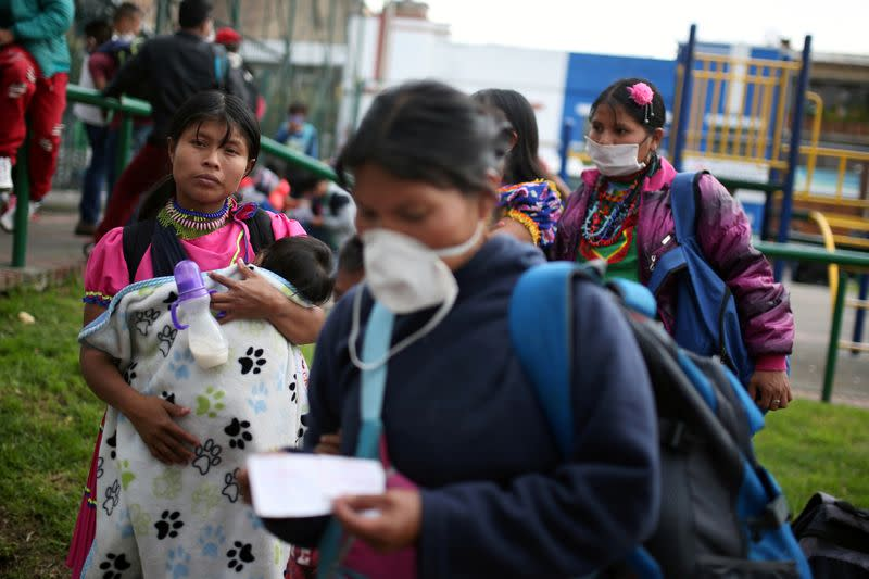 Indigenous people wearing protective face masks as a preventive measure against the spread of the coronavirus disease (COVID-19) carry their belongings after being evicted from a building in Bogota