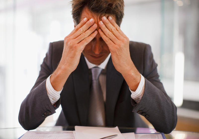 Man in suit holding his head while staring down at his desk.