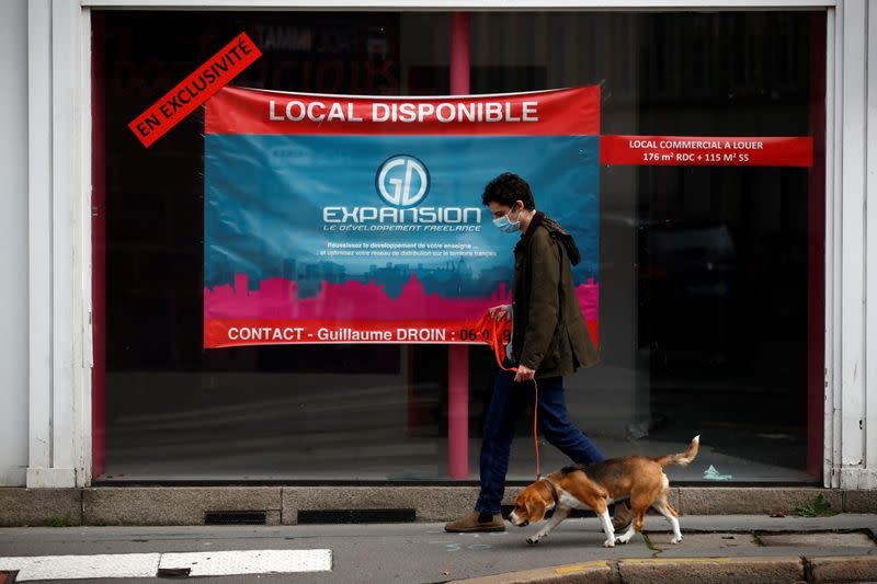 A man walks his dog past a commercial space for rent in a street in Nantes