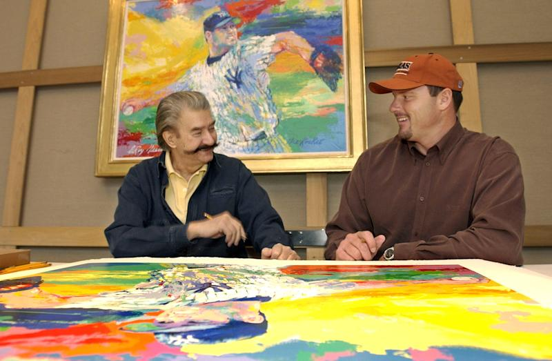 "FILE - In this Nov. 13, 2003 file photo, New York Yankees pitcher Roger Clemens, right, talks to artist Leroy Neiman about baseball while signing limited edition serigraphs based on Neiman's painting ""The Rocket,"" above, of Clemens on the mound in pinstripes, at Neiman's New York studio. Neiman, who is best known for his colorful and energetic paintings of sporting events, died Wednesday, June 20, 2012 in New York. He was 91. (AP Photo/Kathy Willens, File)"