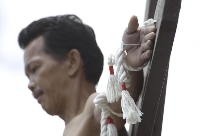 CORRECTS CITY - A Filipino penitent is nailed to the cross during Good Friday rituals Friday, March 29, 2013 in San Juan, Pampanga province, northern Philippines. Several Filipino devotees had themselves nailed to crosses Friday to remember Jesus Christ's suffering and death, an annual rite rejected by church leaders in this predominantly Roman Catholic country. (AP Photo/Aaron Favila)