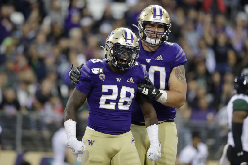 Washington running back Richard Newton (28) celebrates with offensive lineman Jared Hilbers, right, after Newton scored a touchdown against Hawaii during the second half of an NCAA college football game, Saturday, Sept. 14, 2019, in Seattle. Washington won 52-20. (AP Photo/Ted S. Warren)