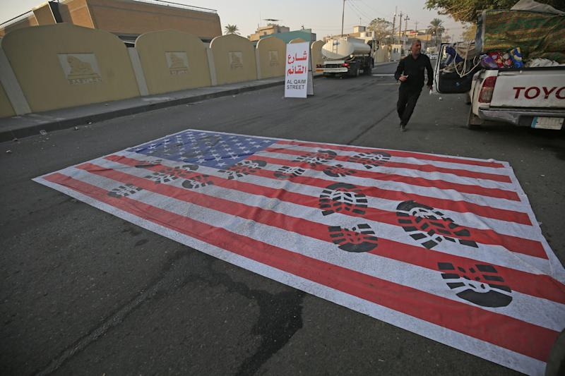 TOPSHOT - A mock US flag is laid on the ground for cars to drive on in the Iraqi capital Baghdad on January 3, 2020, following news of the killing of Iranian Revolutionary Guards top commander Qasem Soleimani in a US strike on his convoy at Baghdad international airport. (Photo by AHMAD AL-RUBAYE / AFP) (Photo by AHMAD AL-RUBAYE/AFP via Getty Images)