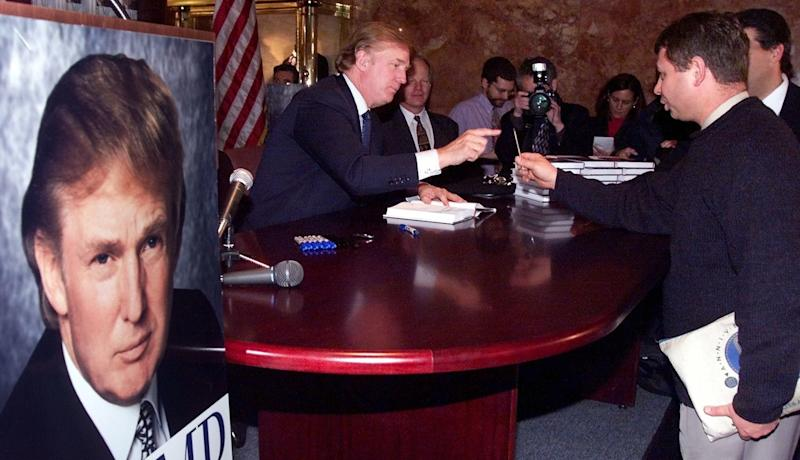 "Donald Trump reaches for a pen as he signs a copy of his new book, ""Trump: The America We Deserve,"" at Trump Towers in New York in January 2000."