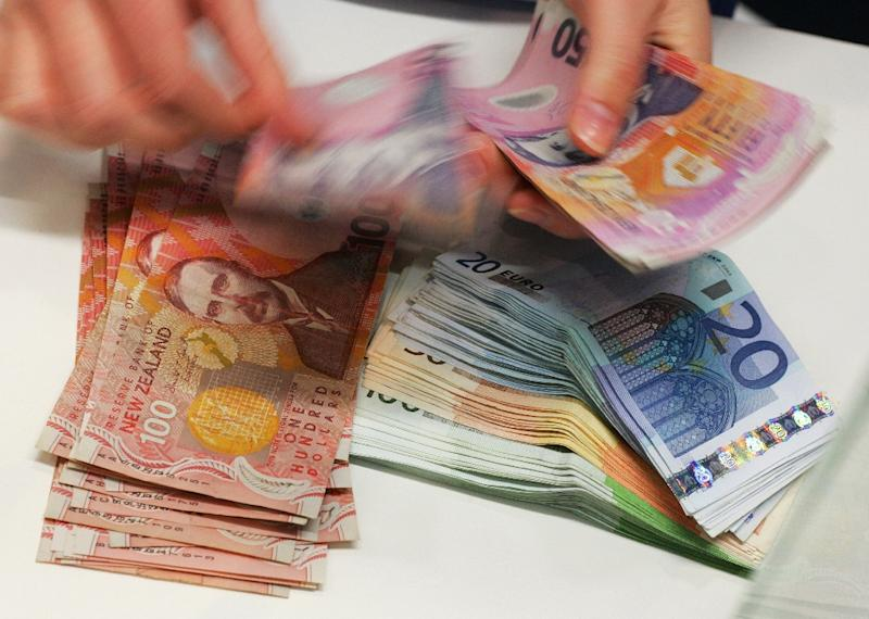 A Currency Exchange Teller Counts Out New Zealand Dollars Alongside Stack Of Euros In Auckland