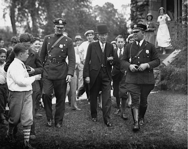 """FILE - In this May 14, 1933 file photo, John D. Rockefeller, Sr. is surrounded by state troopers and admirers as he attended church in Lakewood, N.J. In the early 21st century, members of the economic elite are looking for ways to reduce the nation's growing income inequality for a variety of reasons, from self-interest to pangs of conscience. """"Names like Carnegie, Mellon and Rockefeller_ the (Warren) Buffet and (Bill) Gates of their days - grace universities, museums and medical centers in part because the originators of those fortunes gave back,"""" Harvard Business School professor Michael Norton says. (AP Photo, File)"""