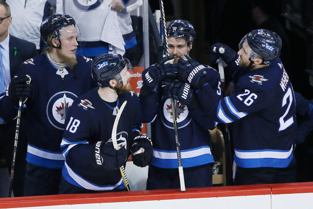 Winnipeg Jets' Patrik Laine (29), Bryan Little (18), Mark Scheifele (55) and Blake Wheeler (26) celebrate the team's 5-0 win over the Minnesota Wild in Game 5 of an NHL hockey first-round playoff series in Winnipeg, Manitoba, Friday, April 20, 2018. (John Woods/The Canadian Press via AP)
