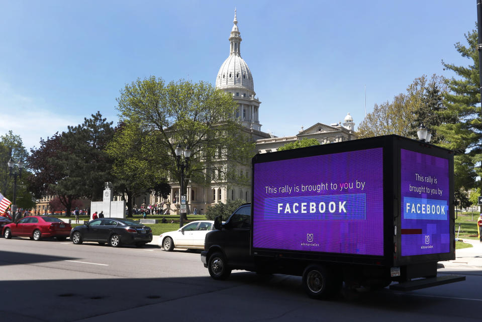 A video sign about Facebook is shown on a truck at the State Capitol during a rally in Lansing, Mich., Wednesday, May 20, 2020. Barbers and hair stylists are protesting the state's stay-at-home orders, a defiant demonstration that reflects how salons have become a symbol for small businesses that are eager to reopen two months after the COVID-19 pandemic began. (AP Photo/Paul Sancya)