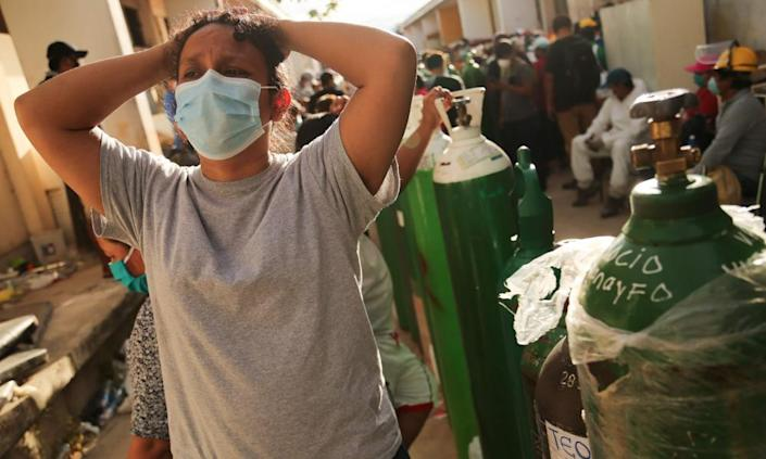 Relatives of coronavirus patients wait to recharge oxygen tanks for their loved ones at the regional hospital in Iquitos on 14 May.