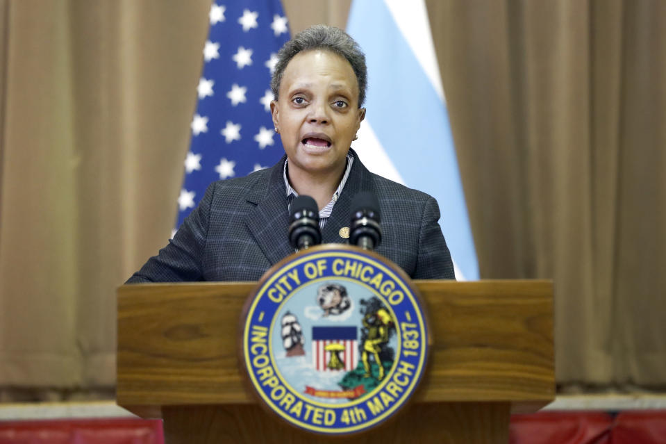 Chicago mayor Lori E. Lightfoot, left, speaks Thursday, Feb. 11, 2021, during a news conference at the William H. Brown Elementary School after a tour of the school. In-person learning for students in pre-k and cluster programs began Thursday, since the district's agreement with Chicago Teachers Union was reached. (AP Photo/Shafkat Anowar,Pool)