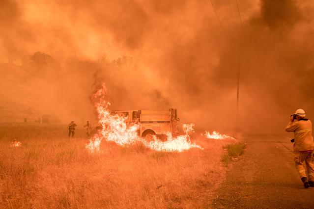 <p>Firefighters scramble to control flames surrounding a fire truck as the Pawnee fire jumps across highway 20 near Clearlake Oaks, Calif. on July 1, 2018. (Photo: Josh Edelson/AFP/Getty Images) </p>
