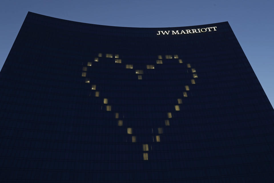 File-This April 7, 2020, file photo shows a heart shining on the side of the JW Marriott, in Indianapolis. Businesses are rethinking political contributions in the wake of the deadly Capitol siege by President Donald Trump's supporters on Wednesday, Jan. 6, 2021. Citigroup confirmed Sunday, Jan. 10, 2021, that it is pausing all federal political donations for the first three months of the year. Others, like Marriott, are only stopping donations to the 147 Republicans who opposed certifying President-elect Joe Biden's election. (AP Photo/Darron Cummings, File)