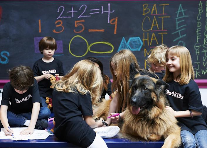 In this Feb. 18, 2013 photo provided by K9s4KIDS, children share time with canine mascot Johnny Cash at the TutorVille HUB in Houston. Schools have beefed up security, staged mock drills and added metal detectors, cameras and alarms to prevent violence. Some think teachers should be armed and the National Rifle Association wants armed police in every American school. Kristi Schiller thinks some special dogs might do the trick. She wants her charity, K9s4KIDS, to do for schools what it's done for police departments in the U.S. - place scores of trained dogs among their ranks through the nonprofit set up in 2009. (AP Photo/K9s4KIDS, Josh Welch)