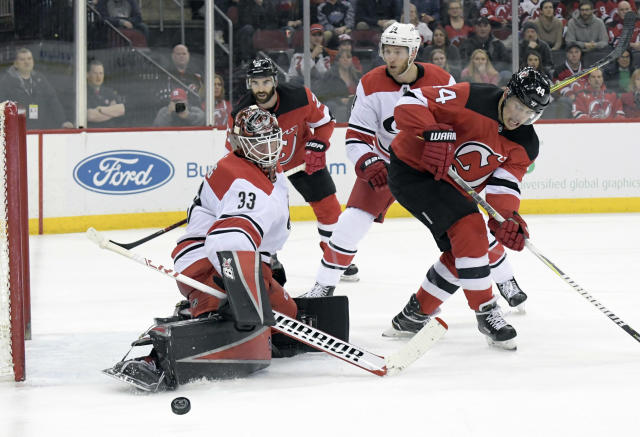 Carolina Hurricanes goaltender Scott Darling (33) deflects the puck as New Jersey Devils center Nico Hischier (13) looks on during the second period of an NHL hockey game Tuesday, March 27, 2018, in Newark, N.J. (AP Photo/Bill Kostroun)