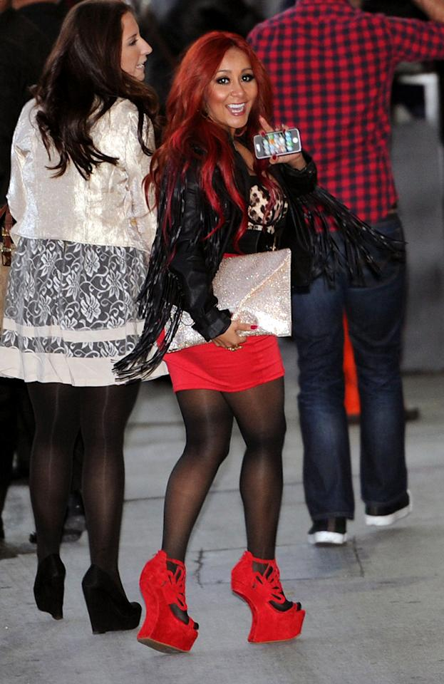 Nicole 'Snooki' Polizzi wears red mini skirt and 6 inch wedges as she heads to a TV interview in LA. The Jersey Shore actress who recently had a baby was seen arriving at the Jimmy Kimmel show in Los Angeles on a cold night in hollywood. The actress braved the weather as she wore the tiny skirt and showed off her post baby body on her may into the TV studio in LA