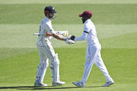 West Indies Jermaine Blackwood, left, shakes hands with New Zealand's Kane Williamson at the close of the New Zealand innings during play on day two of the first cricket test between the West Indies and New Zealand in Hamilton, New Zealand, Friday, Dec. 4, 2020. (Andrew Cornaga/Photosport via AP)