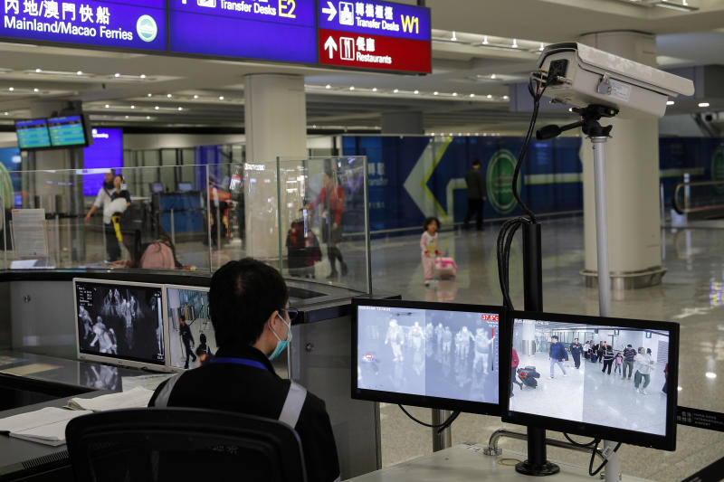 """A health surveillance officer monitors passengers arriving at the Hong Kong International airport in Hong Kong, Saturday, Jan. 4, 2020. Hong Kong authorities activated a newly created """"serious response"""" level Saturday as fears spread about a mysterious infectious disease that may have been brought back by visitors to a mainland Chinese city. (AP Photo/Andy Wong)"""