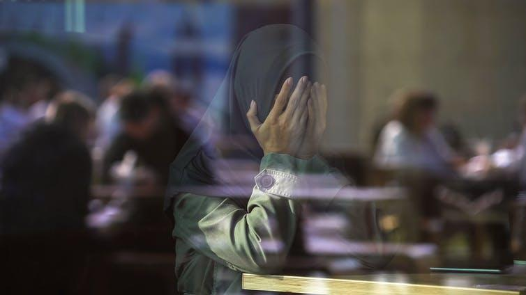 Desperate Muslim female crying in cafe, covering face with hands