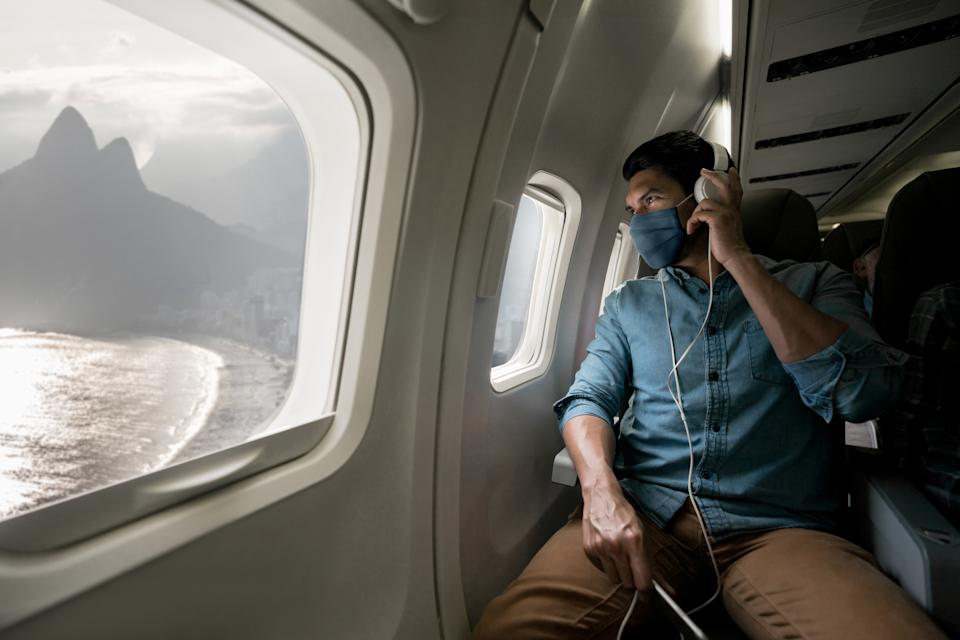 Portrait of a Latin American man traveling by plane wearing a facemask during the COVID-19 pandemic and looking at Rio through the window
