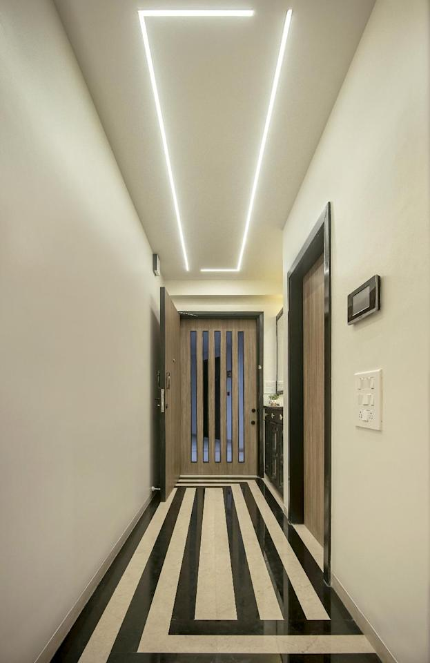 The entryway makes an impact with its high-contrast, black and white flooring. The Art Deco-inspired pattern echoes in the recessed ceiling lighting.