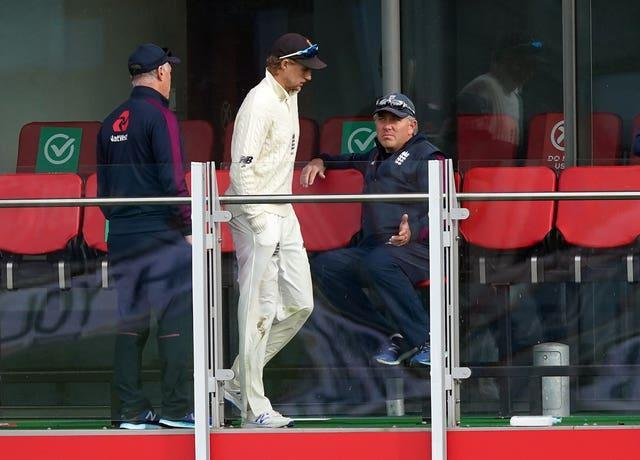 Joe Root, centre, speaks to Chris Silverwood, right
