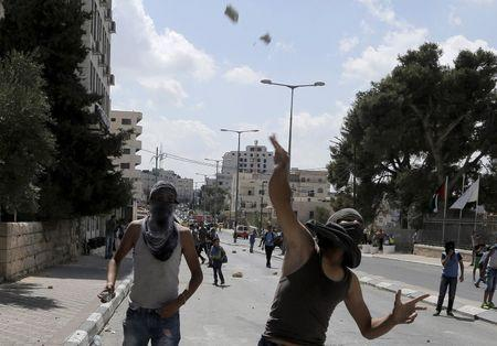 Masked Palestinian protesters throw stones at Israeli troops during clashes in the occupied West Bank city of Bethlehem, September 21, 2015. REUTERS/Ammar Awad