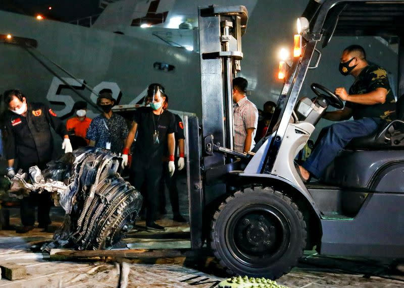 Indonesia Navy personnel uses a forklift to move the turbine of Sriwijaya Air flight SJ 182 on the last day of its search and rescue operation at the Tanjung Priok port in Jakarta