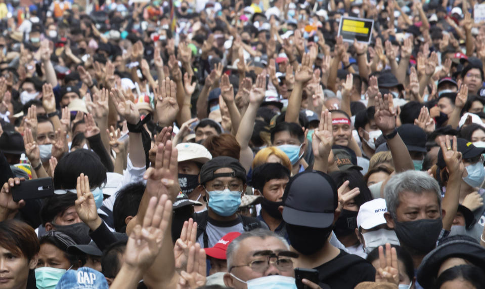 Anti-government protesters raise a three-fingered salute, a symbol of resistance, as they march from Democracy Monument to government house in Bangkok, Thailand, Wednesday, Oct. 14, 2020. Anti-government protesters began gathering Wednesday for a planned rally at Bangkok's Democracy Monument being held on the anniversary of a 1973 popular uprising that led to the ousting of a military dictatorship, amid a heavy police presence and fear of clashes with political opponents. (AP Photo/Sakchai Lalit)