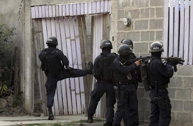 In this April 7, 2013 photo, police break into a home during a shootout that ended in two suspects killed and one officer injured as police carry out an offensive against gang members in Tegucigalpa, Honduras. The officers had surrounded a house where two gangsters had holed up after a chase with police. (AP Photo/Fernando Antonio)