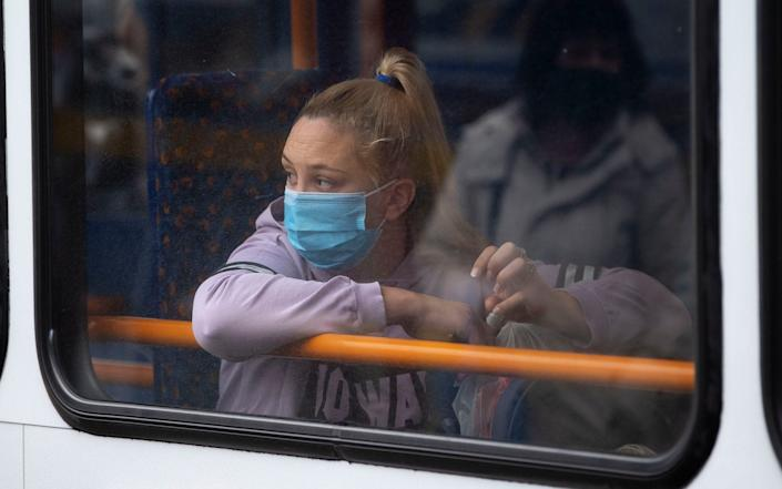 A woman looks out of the window of a bus while wearing a face mask in Wales - Matthew Horwood/Getty Images