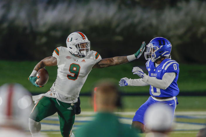 Dec 5, 2020; Durham, North Carolina, USA; Miami Hurricanes tight end Brevin Jordan (9) carries the football against Duke Blue Devils safety Marquis Waters (0) in the first half at Wallace Wade Stadium. Mandatory Credit: Nell Redmond-USA TODAY Sports