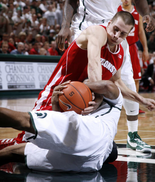 Wisconsin's Ben Brust, top, and Michigan State's Gary Harris wrestle for the ball during the first half of an NCAA college basketball game, Thursday, March 7, 2013, in East Lansing, Mich. (AP Photo/Al Goldis)