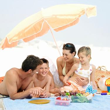 Parents-eating-snacks-with-kids-on-beach_web