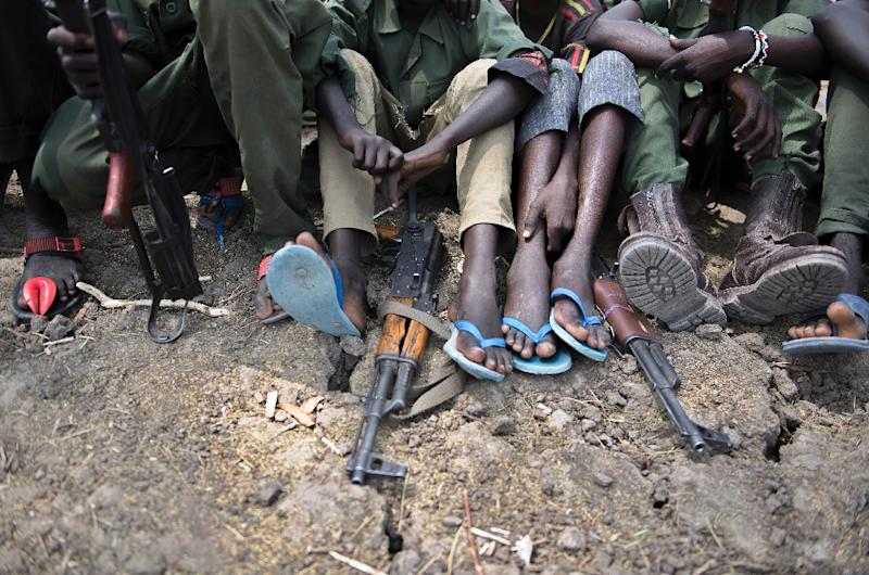 (FILES)-- A file photo taken on February 10, 2015 shows young boys, child soldiers, sitting with their rifles at a ceremony of disarmament, demobilisation and reintegration in Pibor overseen by UNICEF and partners. Warring forces in South Sudan have abducted as many as a thousand more child solders in the latest abuses in the 18-month long civil war, military monitors said on June 25, 2015. AFP PHOTO / CHARLES LOMODONG (AFP Photo/Charles Lomodong)