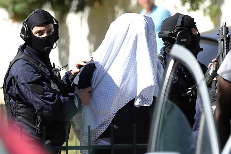 French police escort Yassin Salhi (C), who decapitated his boss in an attack on a gas factory, as they leave his flat in Saint-Priest on June 28, 2015 (AFP Photo/Philippe Desmazes)
