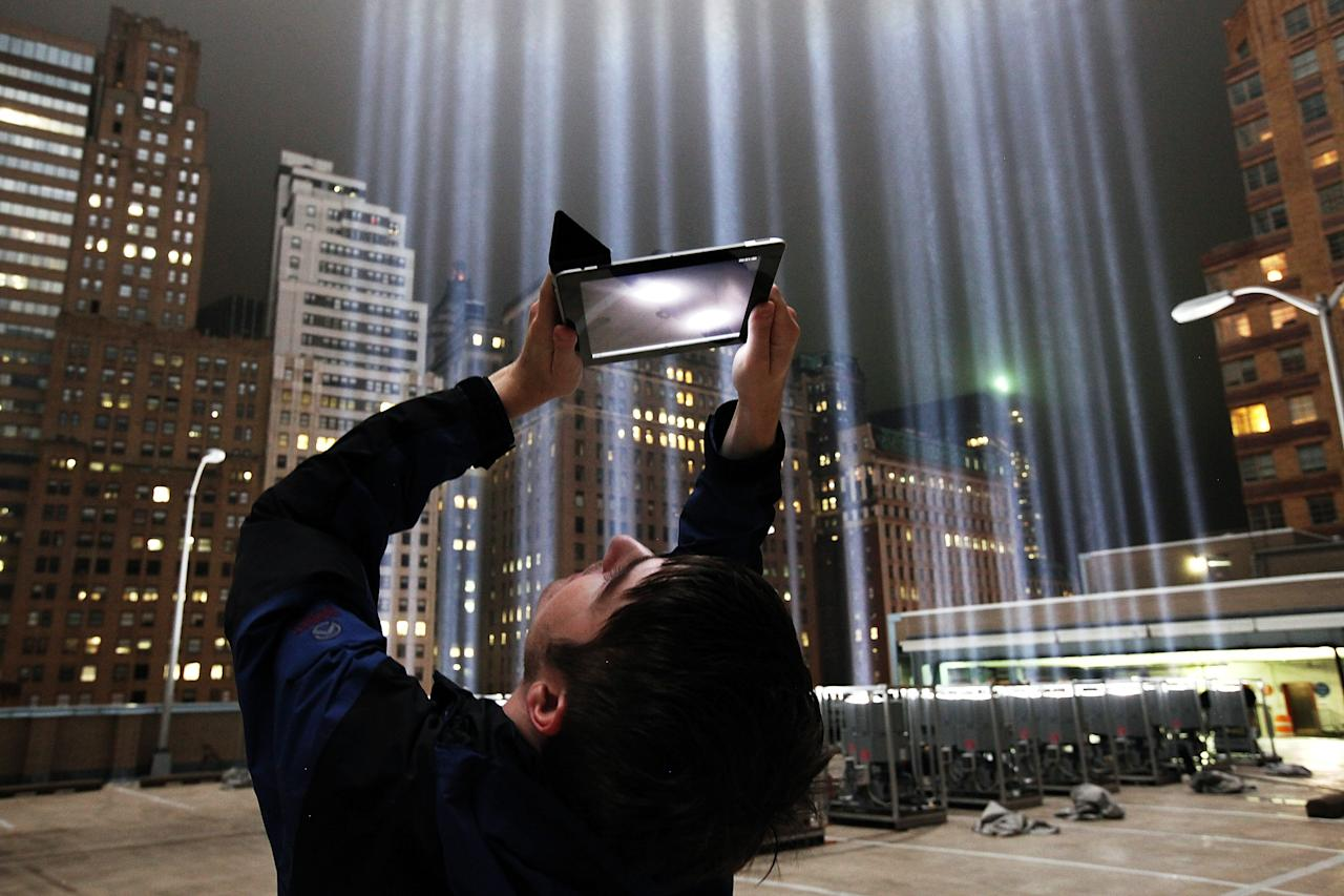 NEW YORK, NY - SEPTEMBER 07:  Lighting Designer Frank Hollenkamp uses his iPad to shoot video of the Tribute in Lights ahead of the tenth anniversary of the September 11 terrorist attacks on September 7, 2011 in New York City. The Tribute in Light is comprised of 88 1-degree beams of 7000 watt searchlights focused into the sky near the site of the World Trade Center in remembrance of the September 11 attacks.  (Photo by Andreas Gebhard/Getty Images)