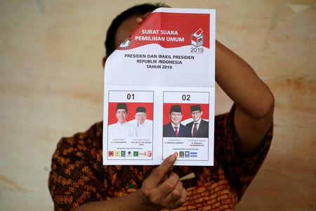 A person holds up a voting ballot during the counting of the Indonesian elections results in Jakarta, Indonesia April 17, 2019. REUTERS/Willy Kurniawan/Files