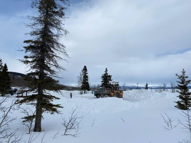 Yukon Parks crews clear snow at a territorial campground earlier this week in preparation for Friday's season opening. (Yukon Parks - image credit)