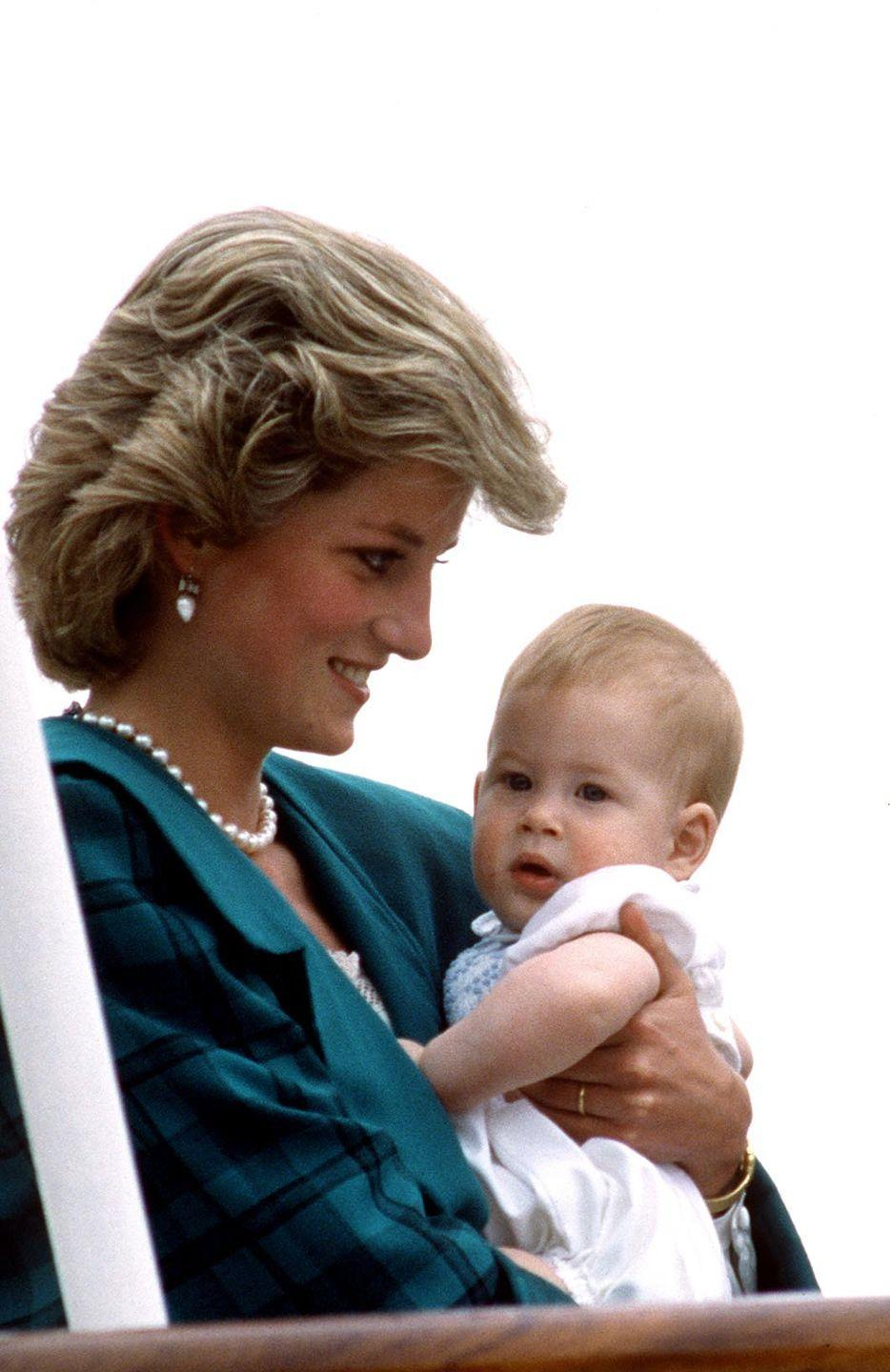 """<p>Harry, 8 months, is cradled by Princess Diana aboard The Royal Yacht Britannia during an official tour of Italy. In the 2017 HBO documentary, <em>Diana, Our Mother: Her Life and Legacy</em>, Harry said of his mother, """"She would just engulf you and squeeze you as tight as possible. And being as short as I was then, there was no escape; you were there and you were there for as long as she wanted to hold you.""""</p>"""