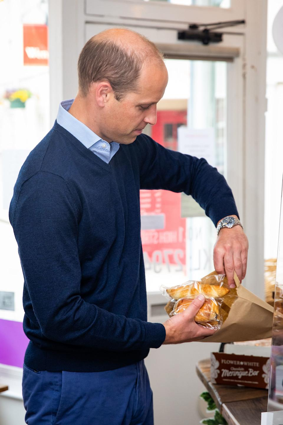 Britain's Prince William, Duke of Cambridge, purchases pain au chocolate during a visit to Smiths the Bakers in the High Street in King's Lynn, eastern England on on June 19, 2020. - The Duke visited the independent business to hear about the impact of the Covid-19 pandemic. (Photo by Aaron Chown / POOL / AFP) (Photo by AARON CHOWN/POOL/AFP via Getty Images)