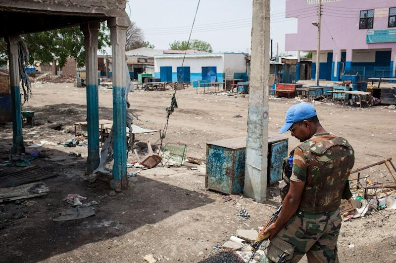 A United Nations peacekeeper looks at the destruction in downtown Malakal, South Sudan on March 4, 2014