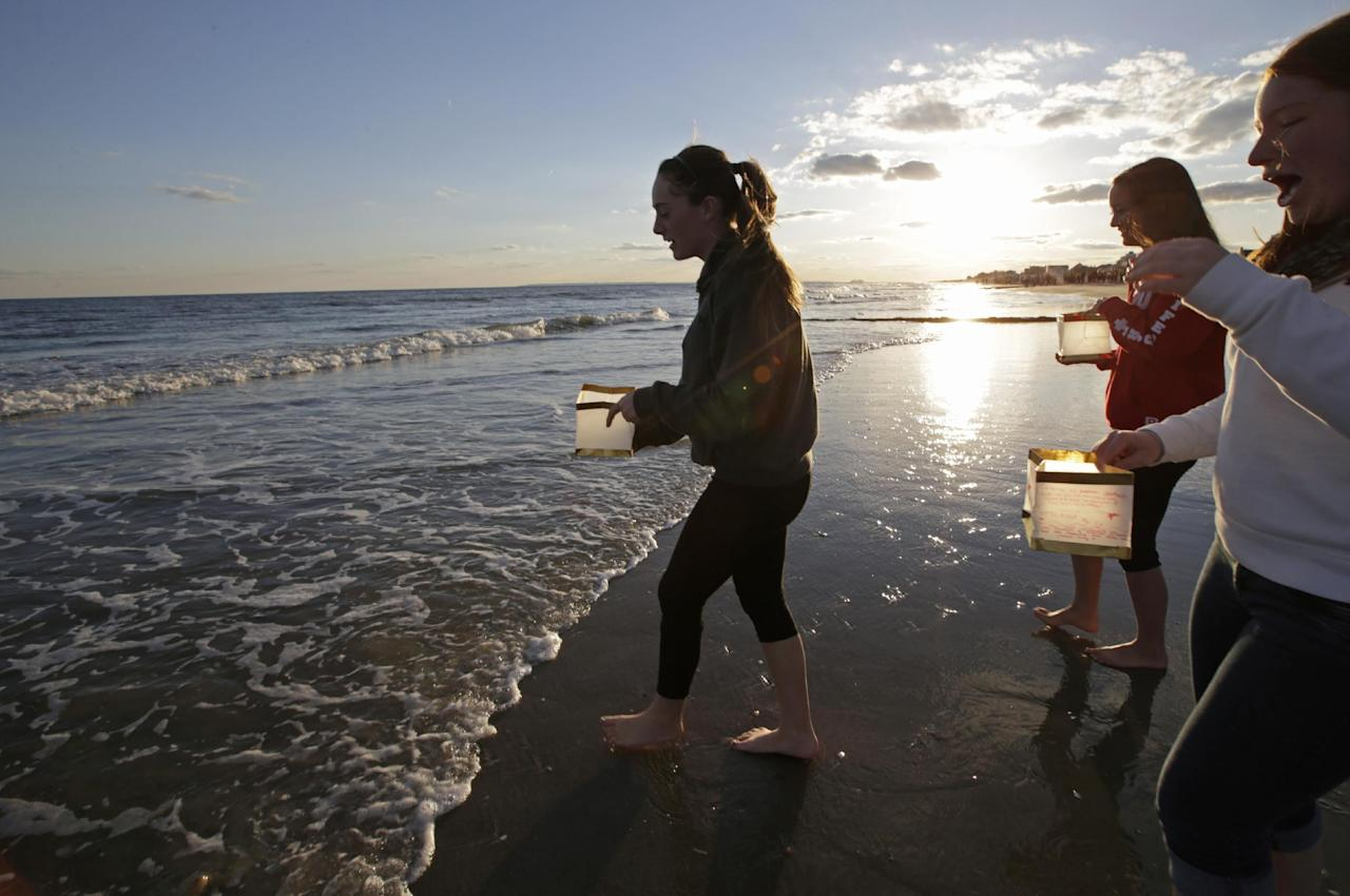 "Young women wade into the ocean to release lanterns with handwritten personal messages on them during a beachside ceremony ""Rockaways Rising: Hands Across the Sand,"" commemorating the one year anniversary of Superstorm Sandy, Sunday, Oct. 27, 2013, in New York. The actual one year anniversary of Superstorm Sandy is Tuesday, Oct. 29. (AP Photo/Kathy Willens)"