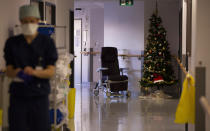 A Belgian Army medic works in the COVID-19 wing with a Christmas tree in the background at the St. Michiel Hospital in Brussels, Tuesday, Nov. 24, 2020. The Belgian military has been called into several hospitals and care homes to alleviate the stress on healthcare personnel. (AP Photo/Virginia Mayo)