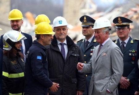 Britain's Prince Charles speaks with an Italy's Civil Protection agency member during his visit to the town of Amatrice, which was levelled after an earthquake last year, in central Italy April 2, 2017.  REUTERS/Alessandro Bianchi